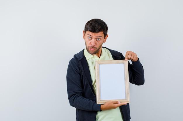 Hübscher mann, der einen fotorahmen in einem lässigen outfit hält