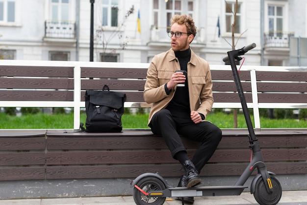 Hübscher mann, der einen kaffee draußen genießt