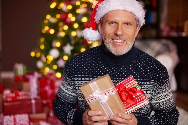 Hübscher mann, der einige geschenkboxen hält