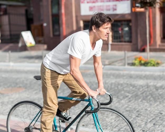 Hübscher mann, der fahrrad fährt, um zu arbeiten