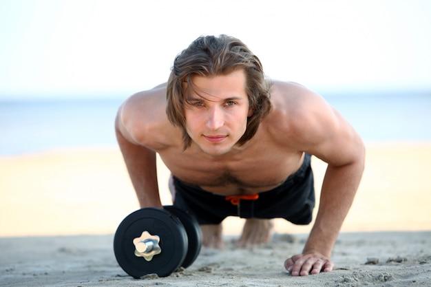 Hübscher mann, der fitnessübungen am strand tut