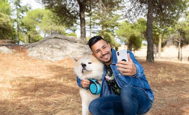 Hübscher mann, der fotos mit seinem hund macht