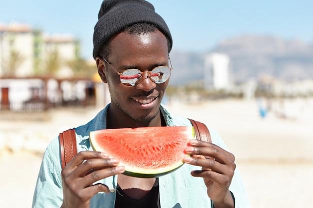 Hübscher mann, der frische saftige wassermelone genießt