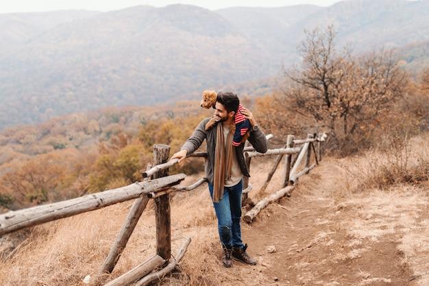 Hübscher mann der gemischten rasse, der sich auf den zaun stützt und seinen aprikosenpudel auf schulter hält, während er schöne ansicht betrachtet. im hintergrund wald und berge, herbstzeit.