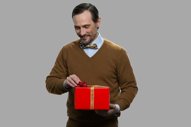 Hübscher mann, der geschenkbox auf grauem hintergrund hält. romantisches geschenk zum jubiläum oder zum geburtstag.