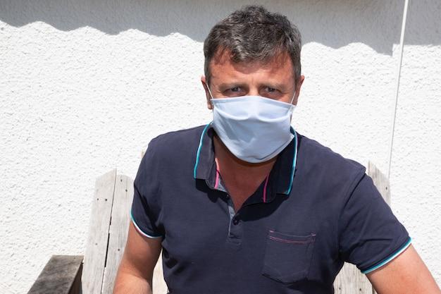 Hübscher mann, der gesichtshygienemaskenase im freien handgemachten stoff in coronavirus-pandemiekrankheit trägt