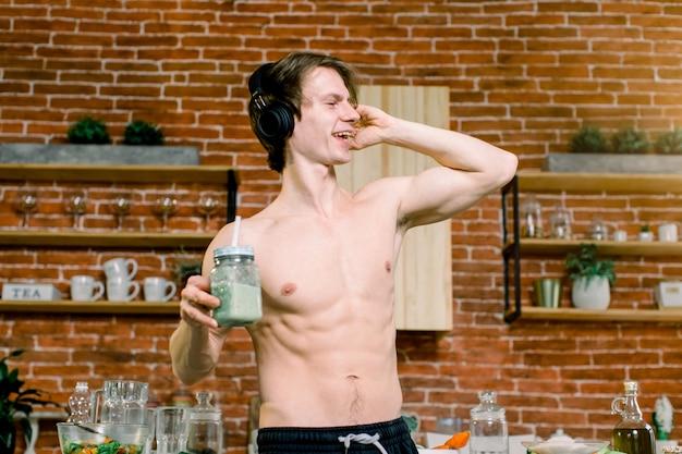 Hübscher mann, der grünen smoothie in der küche trinkt. junger mann hört musik in kopfhörern, trinkt smoothie beim tanzen. gesunder lebensstil und essen