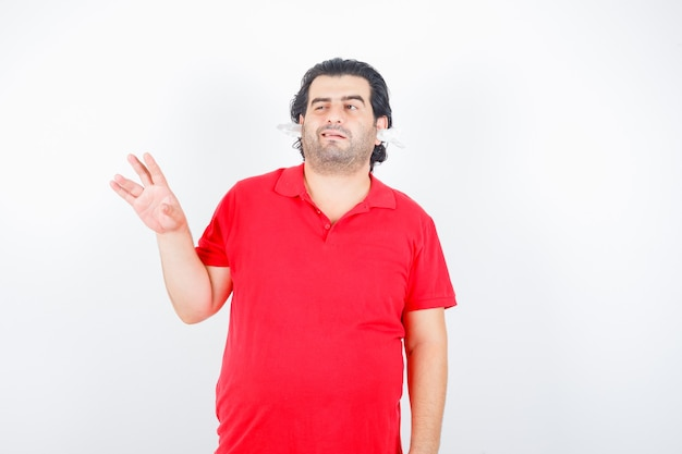 Hübscher mann, der hand hebt, zwinkert, mit servietten in den ohren im roten t-shirt steht und unentschlossen aussieht. vorderansicht.