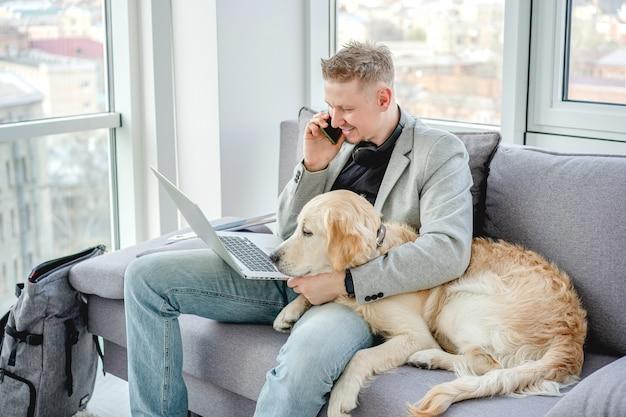 Hübscher mann, der hund während der arbeit kuschelt