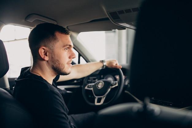 Hübscher mann, der im auto sitzt und es testet