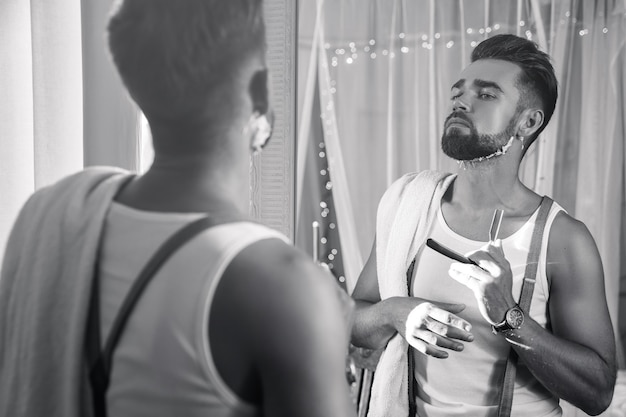 Hübscher mann, der in den spiegel schaut und seinen bart mit einem rasiermesser rasiert
