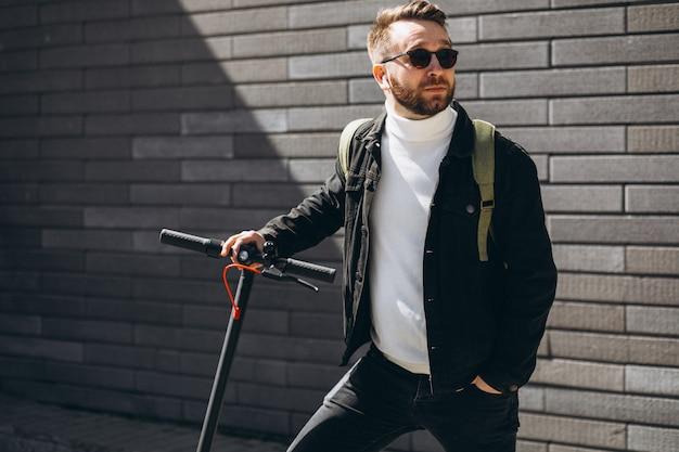 Hübscher mann, der in der stadt auf roller reitet