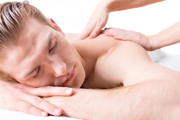 Hübscher mann, der in einem spa-salon liegt, der eine tiefe geweberückenmassage genießt.