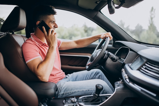 Hübscher mann, der in seinem auto fährt