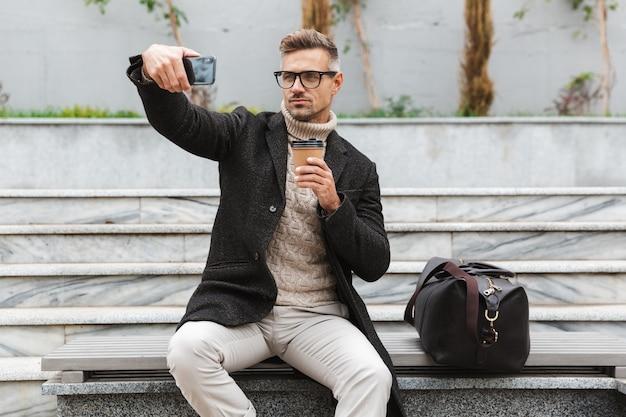 Hübscher mann, der jacke trägt, die ein selfie nimmt, während draußen sitzt und tasse kaffee zum mitnehmen hält