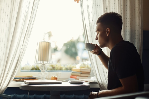 Hübscher mann, der kaffee in einem restaurant trinkt.