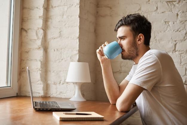 Hübscher mann, der kaffee nach freiberuflicher arbeit trinkt