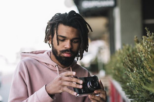 Hübscher mann, der kamera mittlerer schuss hält