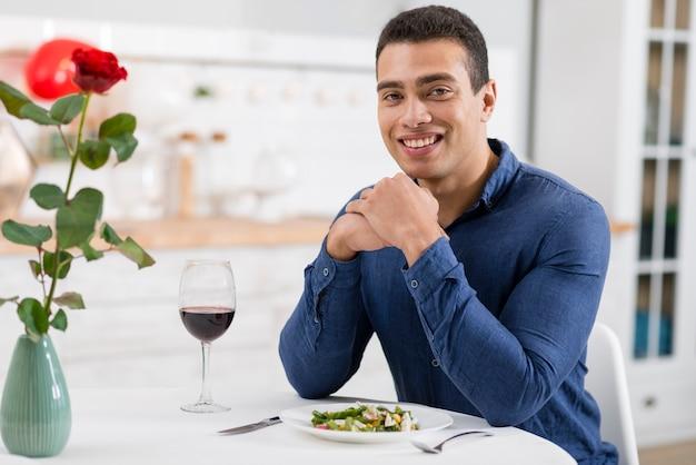 Hübscher mann, der lächelt, während er am tisch sitzt
