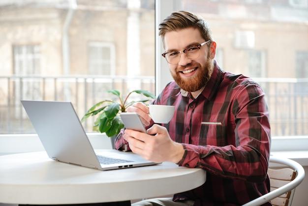 Hübscher mann, der laptop-computer und handy benutzt.