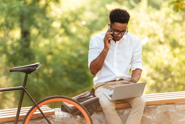Hübscher mann, der laptop-computer verwendet, der durch telefon spricht.