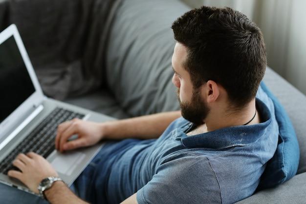 Hübscher mann, der laptop zu hause benutzt. telearbeitskonzept
