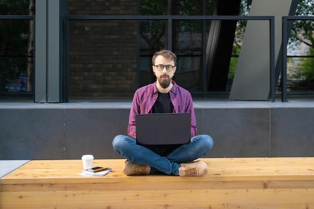 Hübscher mann, der mit gekreuzten beinen auf holzbank mit laptop sitzt
