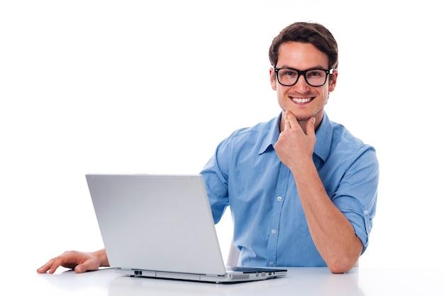 Hübscher mann, der mit laptop arbeitet