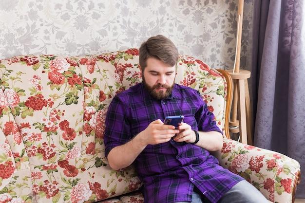 Hübscher mann, der mit seinem smartphone im wohnzimmer eine sms schreibt