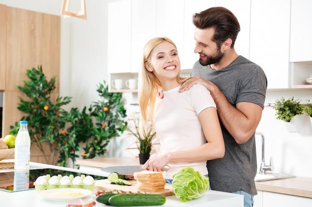 Hübscher mann, der mit seiner jungen freundin zu hause kocht