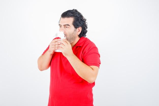 Hübscher mann, der mit servietten in den nasenlöchern steht, serviette in den händen im roten t-shirt hält und erschöpft aussieht. vorderansicht.