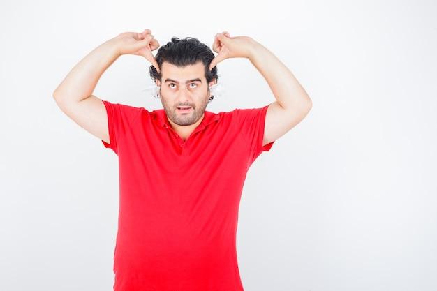 Hübscher mann, der mit servietten in den ohren steht, zeigefinger auf schläfen im roten t-shirt setzt und nachdenklich aussieht. vorderansicht.
