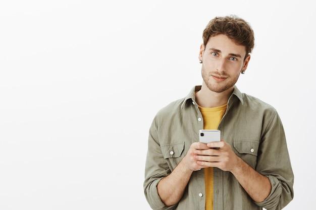 Hübscher mann, der mit smartphone im studio aufwirft