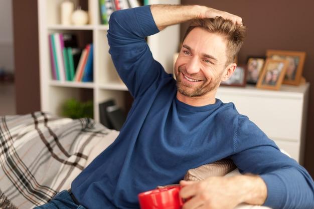 Hübscher mann, der mit tasse kaffee zu hause entspannt