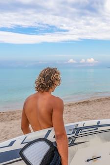 Hübscher mann, der mit weißem leerem surfbrett geht, wartet auf welle, um fleck am meeresozeanufer zu surfen