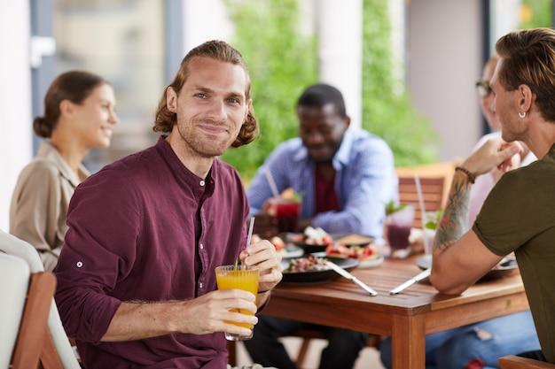 Hübscher mann, der mittagessen mit freunden im cafe genießt