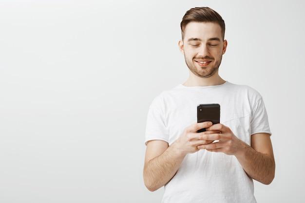 Hübscher mann, der mobile anwendung verwendet. guy messaging mit smartphone