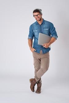 Hübscher mann, der modebrille und wollhut mit laptop trägt