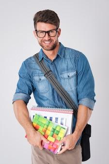 Hübscher mann, der modebrille und wollhut mit notizbuch und schultasche trägt