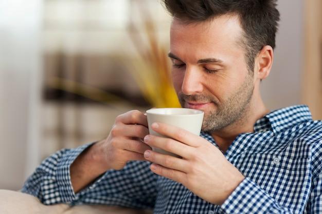 Hübscher mann, der morgenkaffee schmeckt