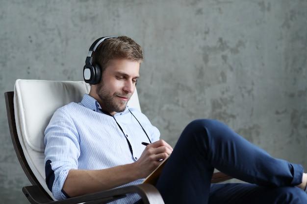 Hübscher mann, der musik auf kopfhörern hört