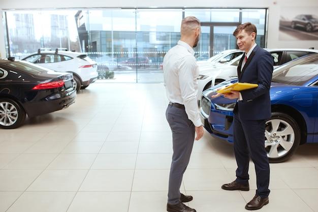 Hübscher mann, der neues auto im autohaus kauft