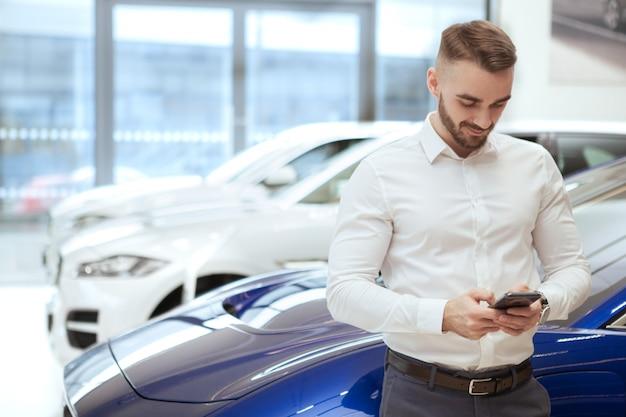 Hübscher mann, der neues auto im autohaus wählt