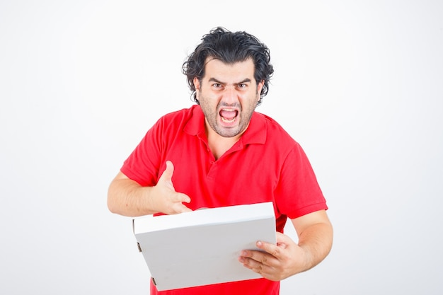 Hübscher mann, der papierkasten hält, hand auf ihn mit wütender weise in rotem t-shirt streckend und wütend, vorderansicht schauend.