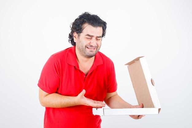 Hübscher mann, der papierkiste öffnet, hand mit enttäuschter weise in rotem t-shirt dazu streckt und enttäuscht sieht, vorderansicht.