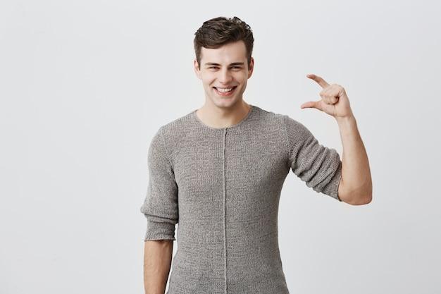 Hübscher mann, der pullover trägt, der etwas kleines mit den händen zeigt, während er gestikuliert und breit lächelt. dunkelhaariges kaukasisches männliches model, das die größe von etwas demonstriert
