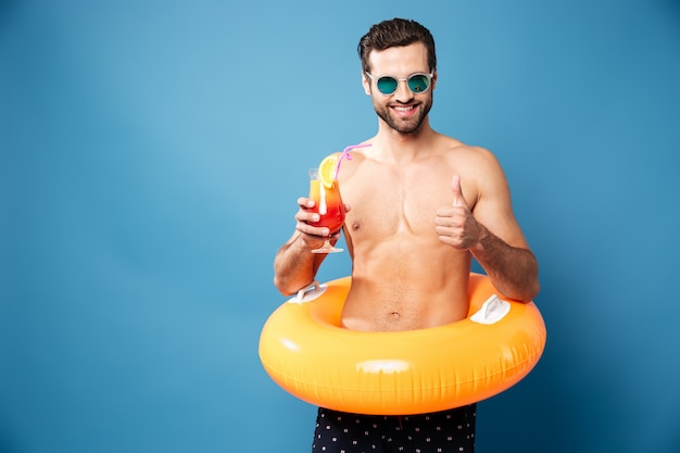 Hübscher mann, der schwimmkreis und cocktail hält