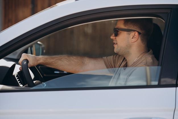 Hübscher mann, der sein auto fährt