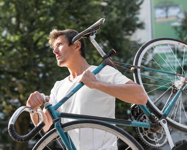 Hübscher mann, der sein fahrrad draußen trägt