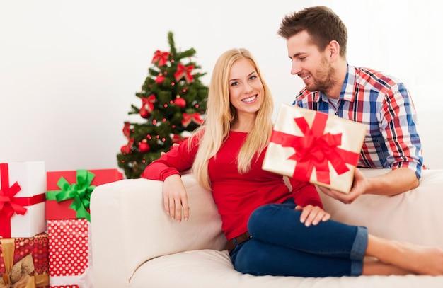 Hübscher mann, der seine freundin mit weihnachtsgeschenk überrascht
